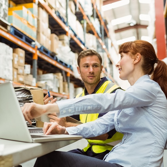Two warehouse employees looking at a laptop